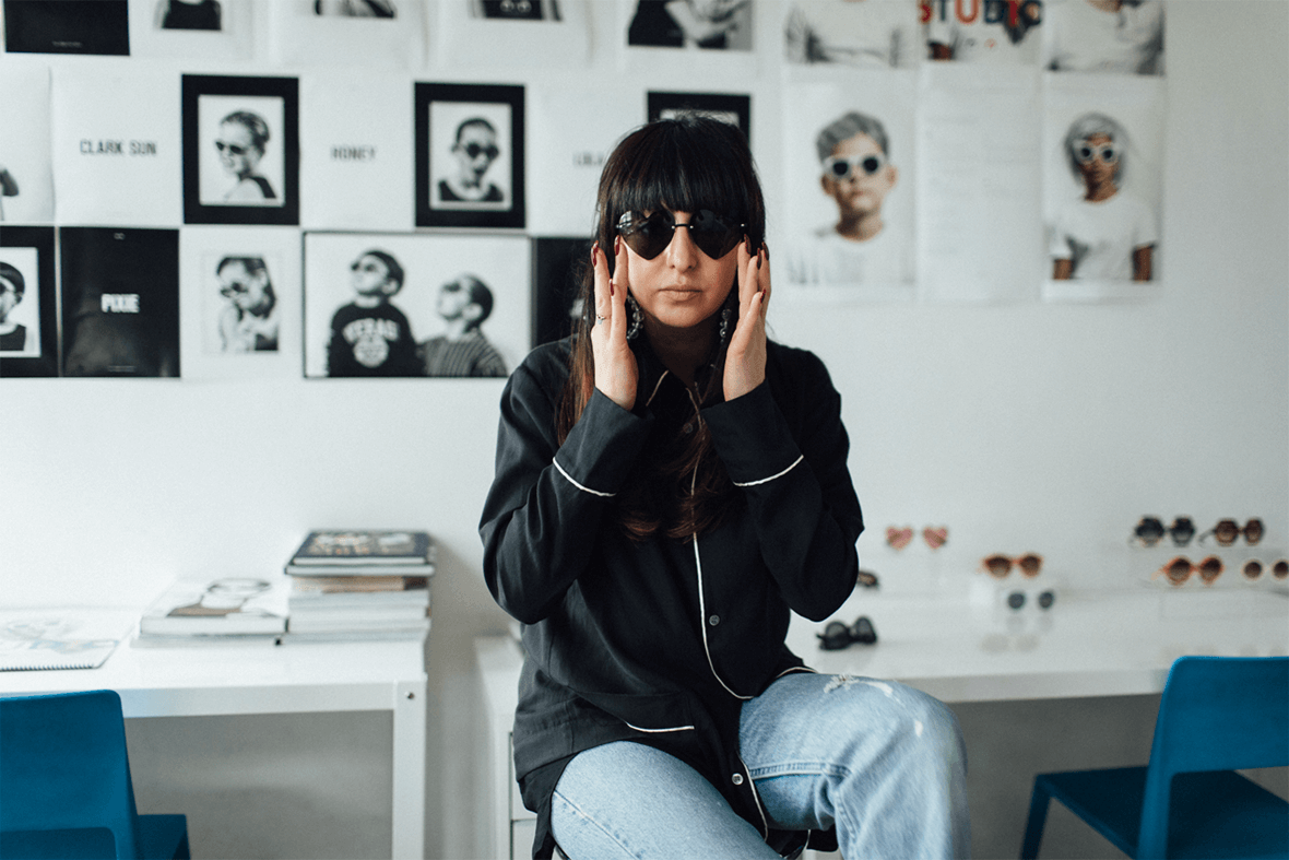 Shiva Shabani wears sunglasses and the Native Shoes Jefferson 2.0 low on a stool in her studio for Sons and Daughters eyewear.