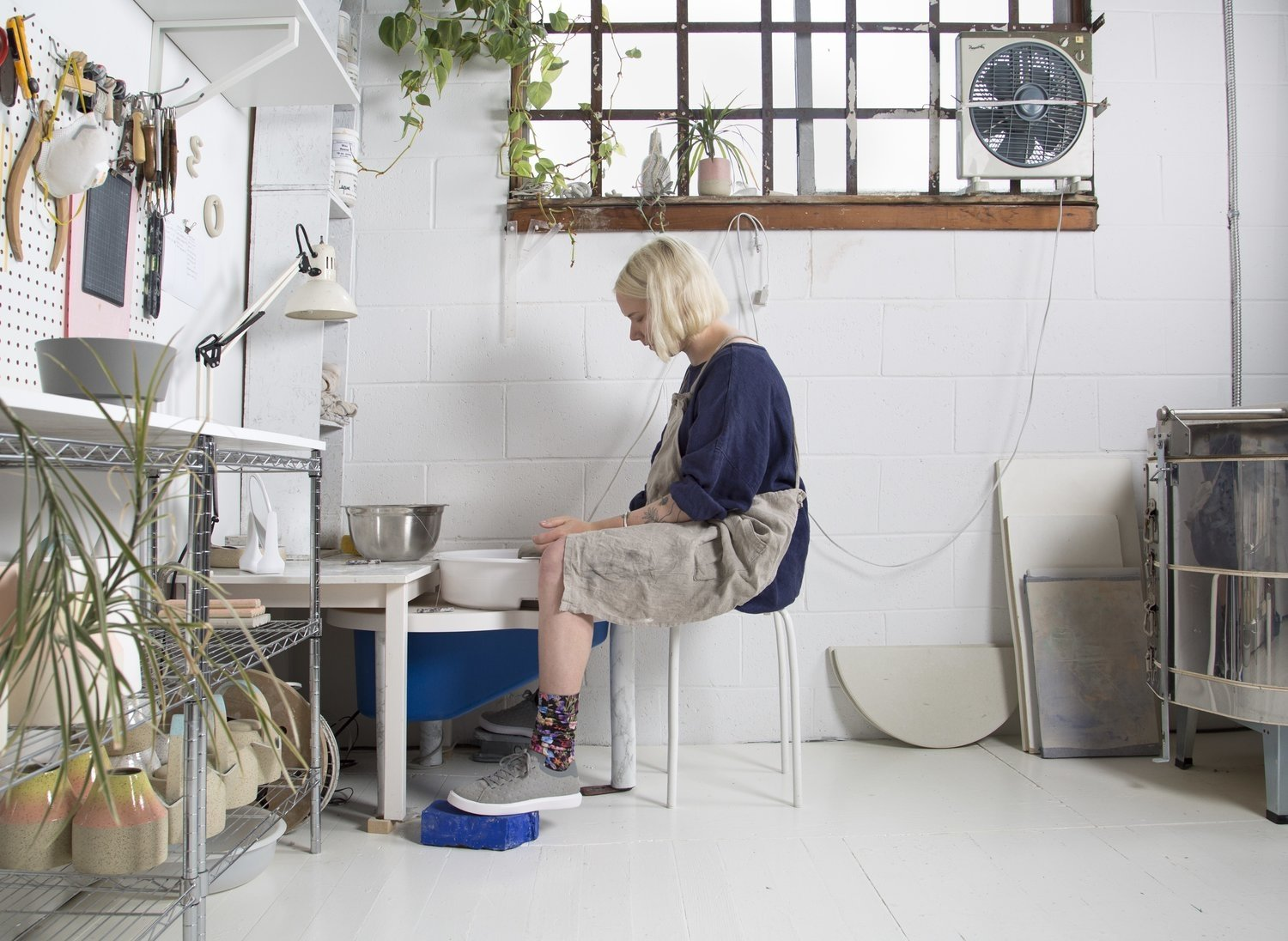 Woman with apron sitting on stool making pottery