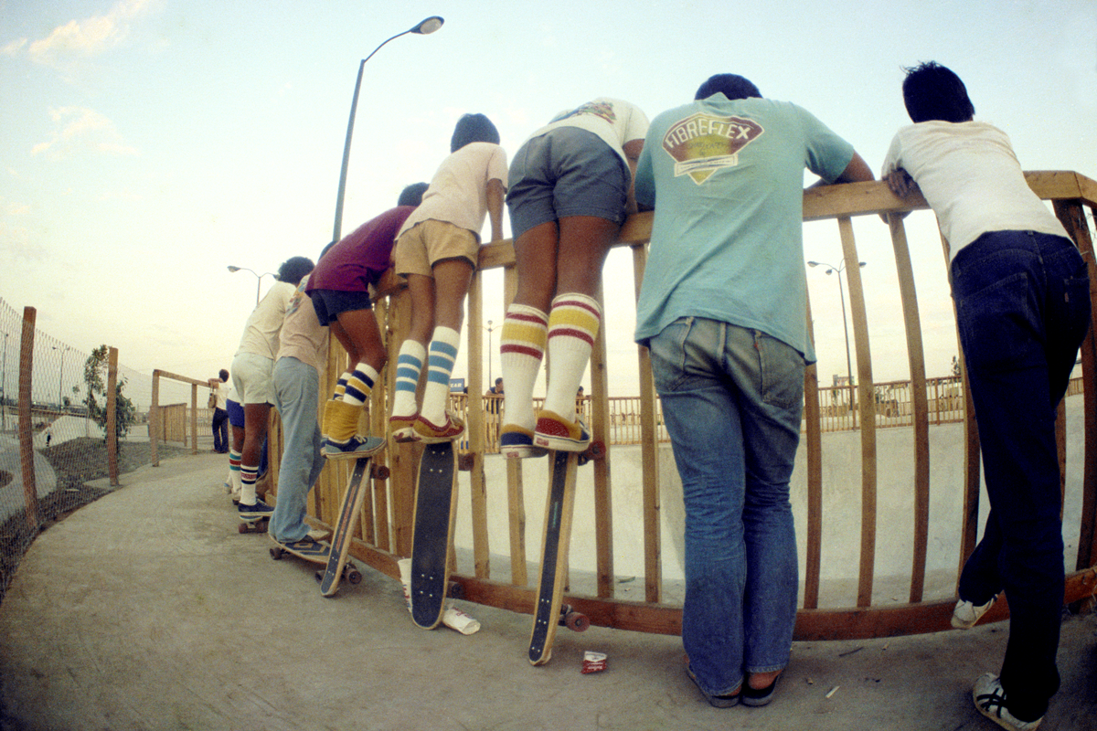 Hugh Holland photograph of kids leaning against a fence watching a skateboarder
