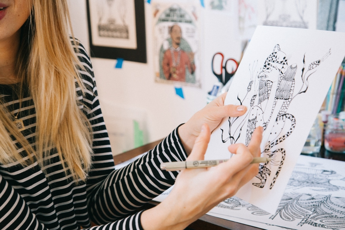 Ola Volo holding a sketch in her studio.