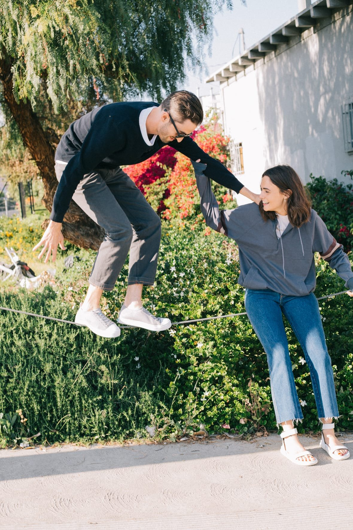 Guy balancing on suspended rope wearing grey sneakers holding shoulder of sitting girl who laughs while wearing white sandals