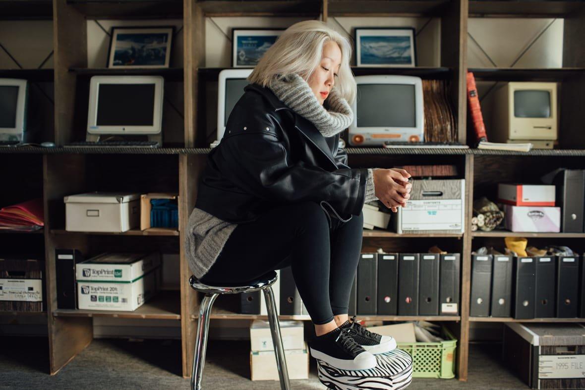 Oribu Yokota sits on a stool in her studio wearing the Jefferson 2.0 Liteknit in black