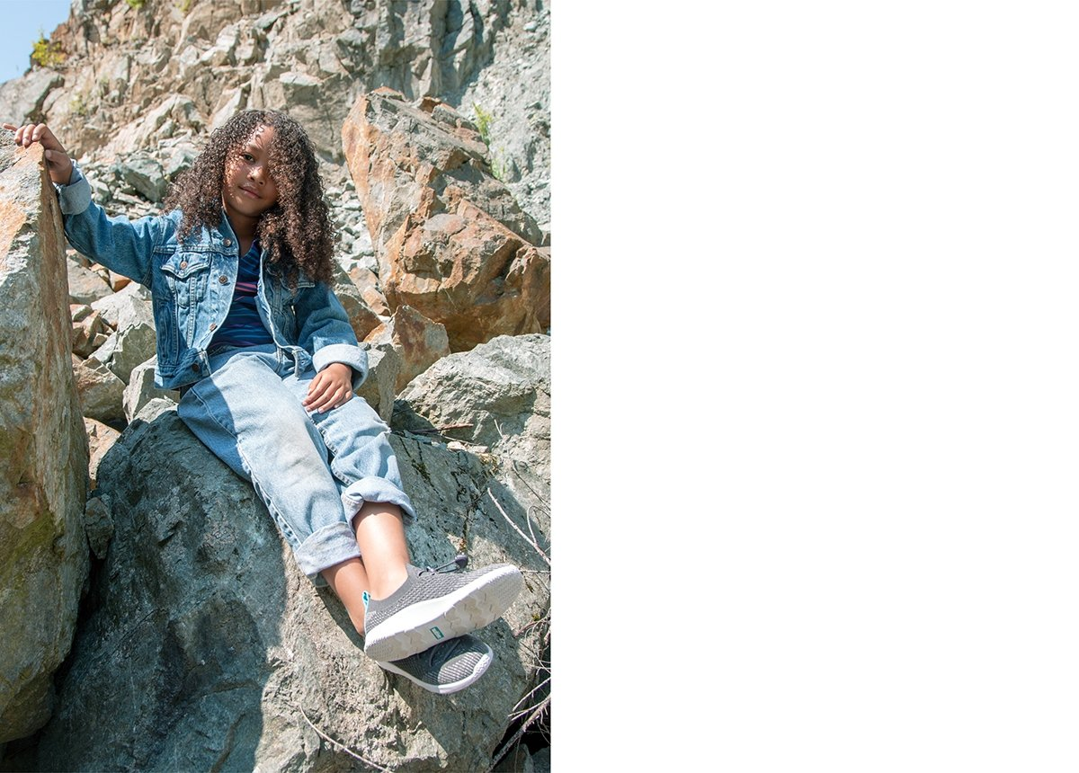 Girl is sitting on a rock and wearing slip on knit sneakers.