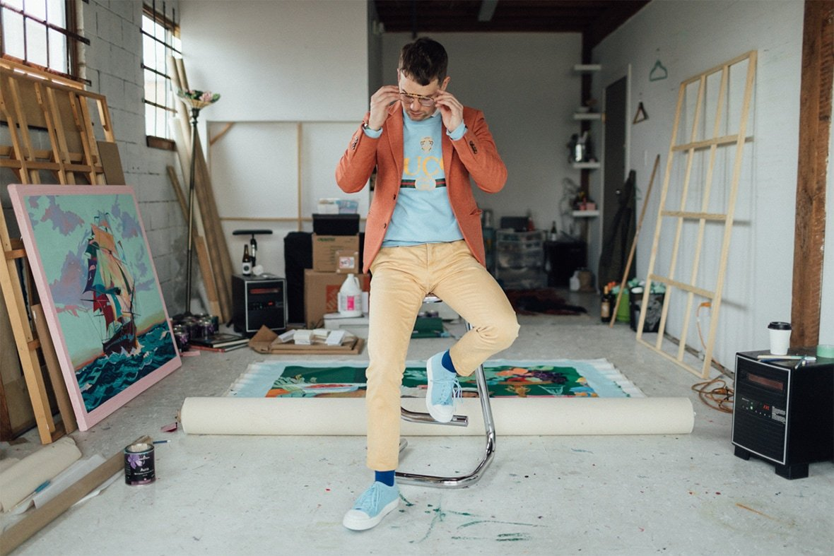 Artist Andy Dixon in his studio sitting on a stool wearing Native Shoes Jefferson 2.0
