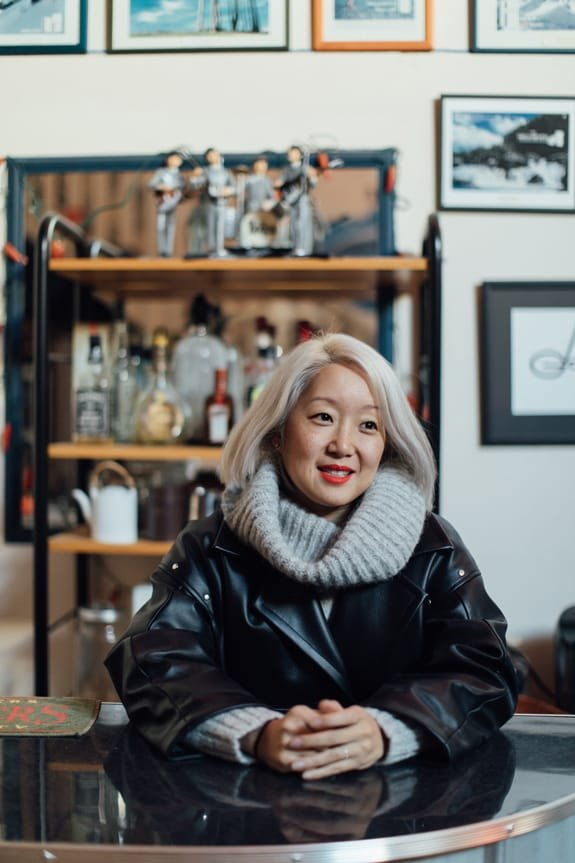 Oribu Yokota smiling and leaning against a vintage bar