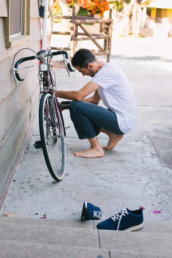 Guy crouching down to fix bike wheel in bare feet, with navy slip-on sneakers sitting nearby