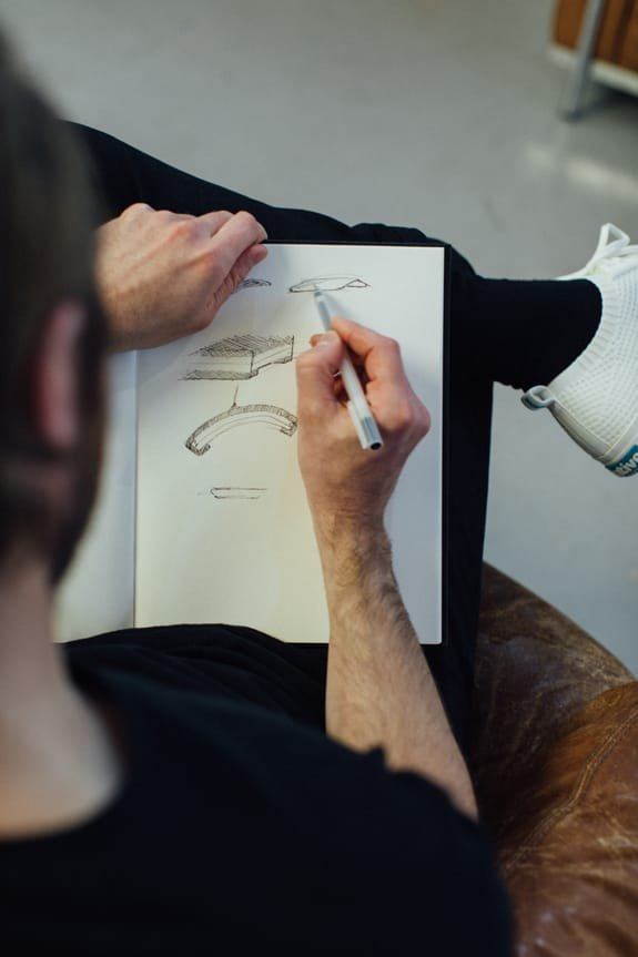 An ANDlight designer sketching lamps