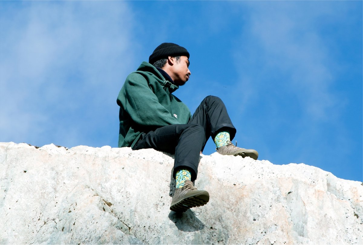 Guy wearing cool sneakers sits on rocky cliff.