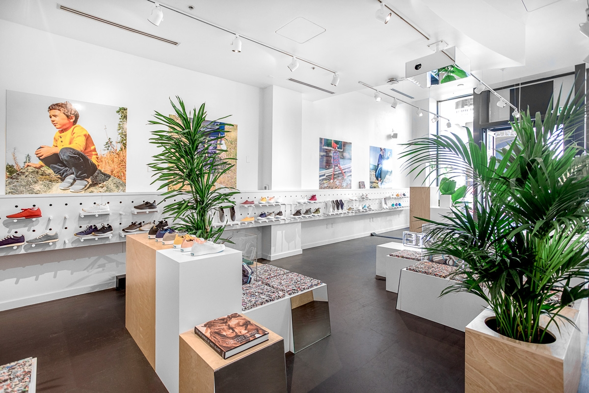 The Native Shoes Santana Row store interior showing green fern plants, recycled seating mats made through The Remix Project, and Native Shoes footwear along the wall.