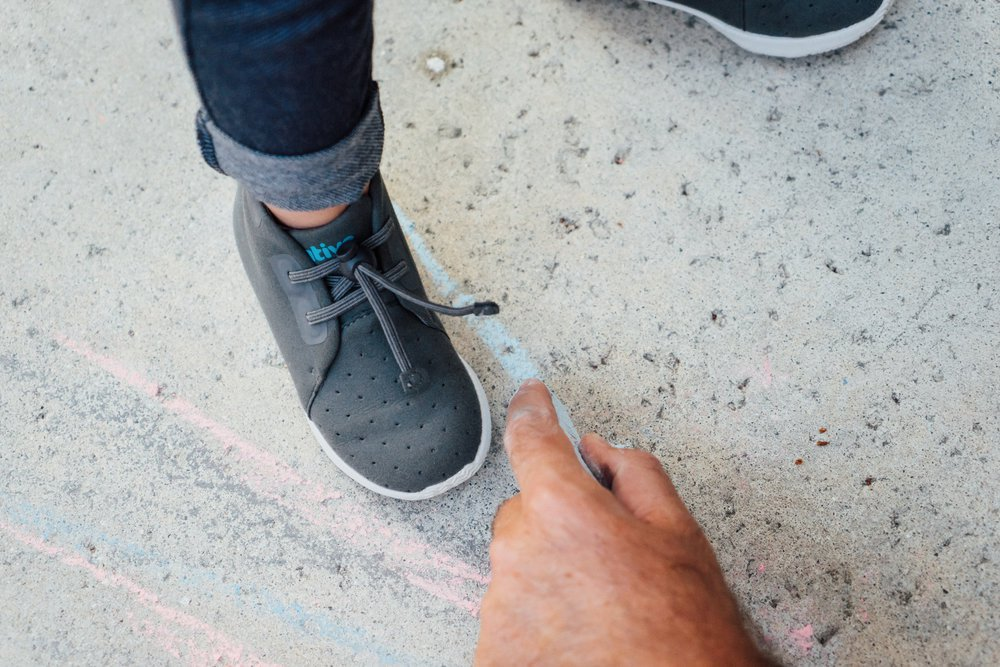 close-up view of boy in grey shoes and men's hand drawing on floor with blue chalk