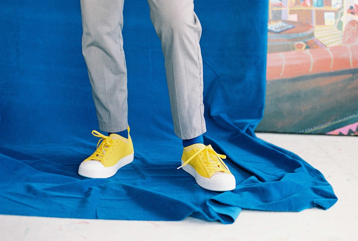 Wearing yellow Native Shoes Jefferson 2.0 on a blue backdrop