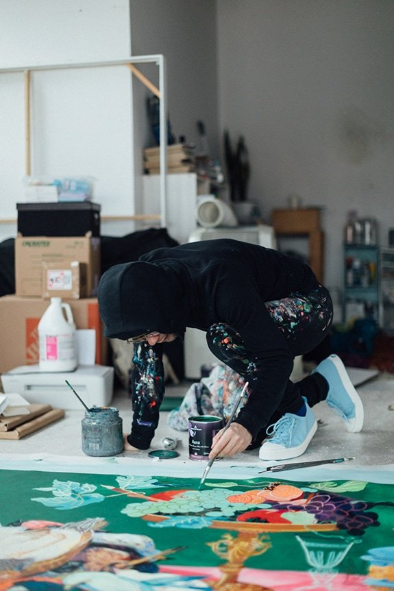 Artist Andy Dixon paints on floor wearing black hoody and Jefferson Sneakers by Native Shoes.