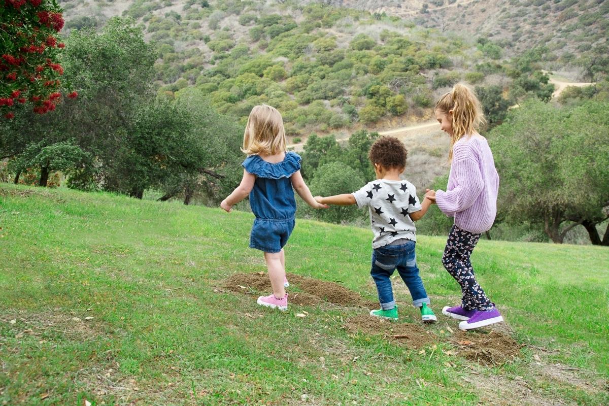 Three kids holding hands walk on a grass field.