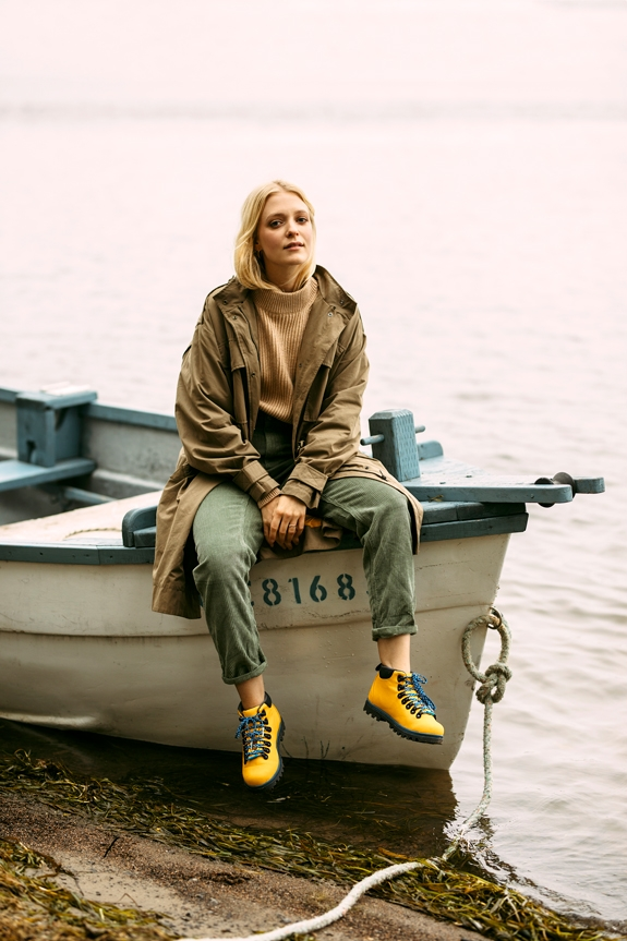 Woman sitting on a docked rowboat wearing the Native Shoes Fitzsimmons Treklite hiking boots