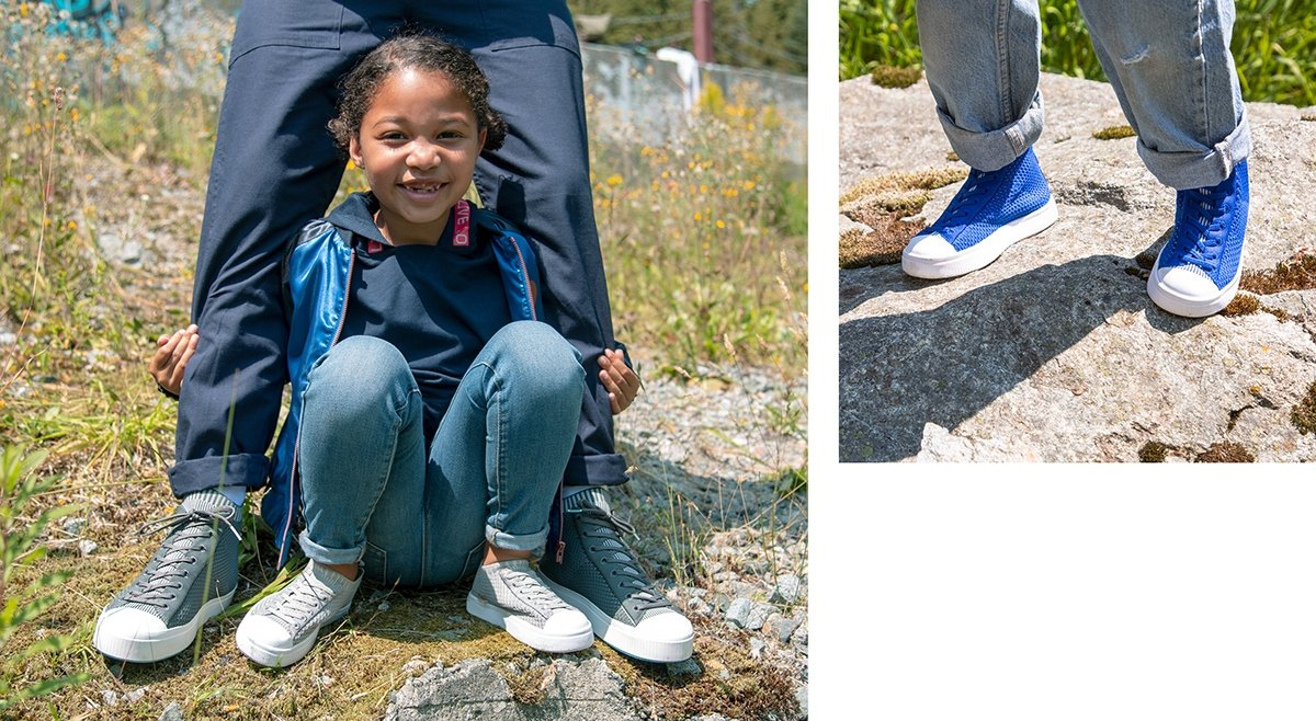 Girl is crouching and wearing slip on knit sneakers. Girl is wearing blue high top sneakers.