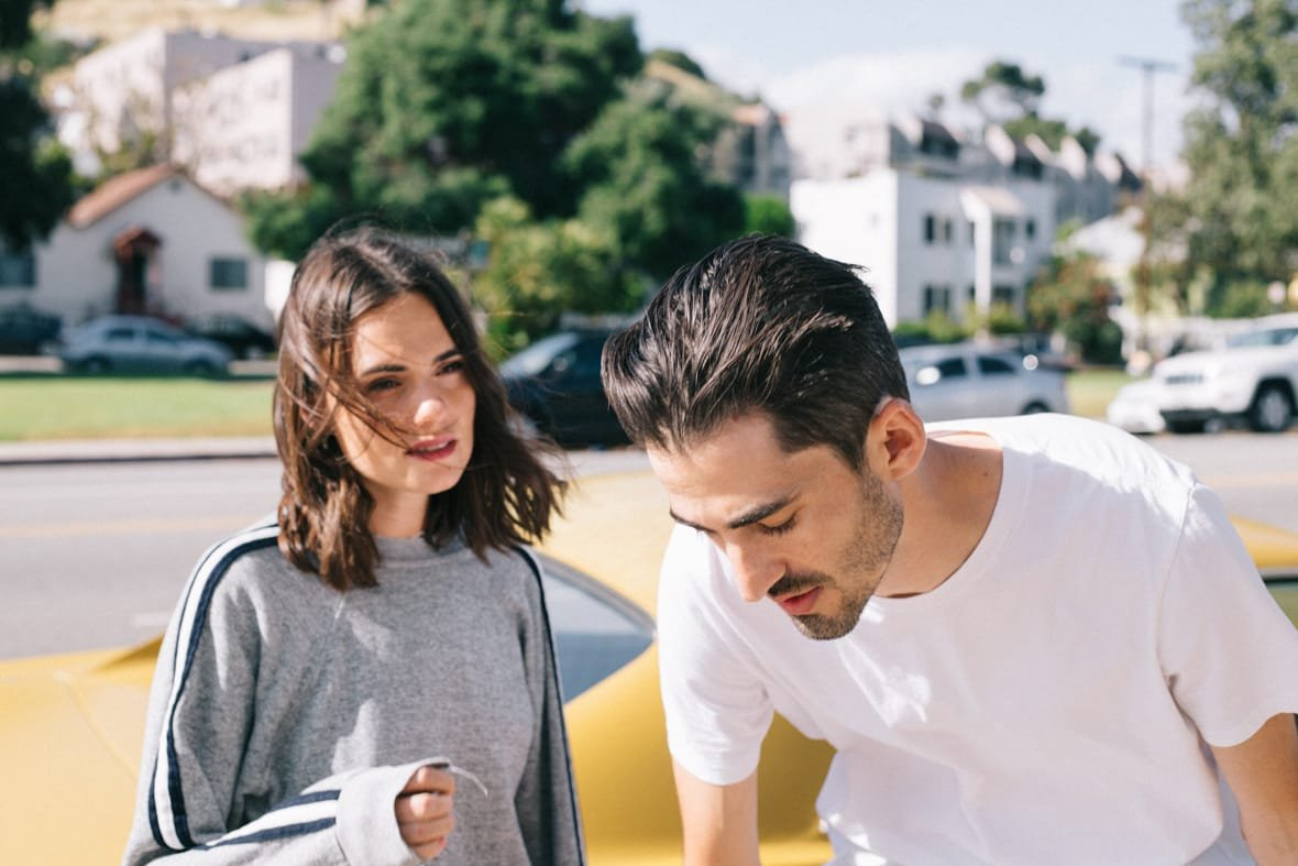 Girl with wind-blown hair speaking to guy in front of yellow sports car