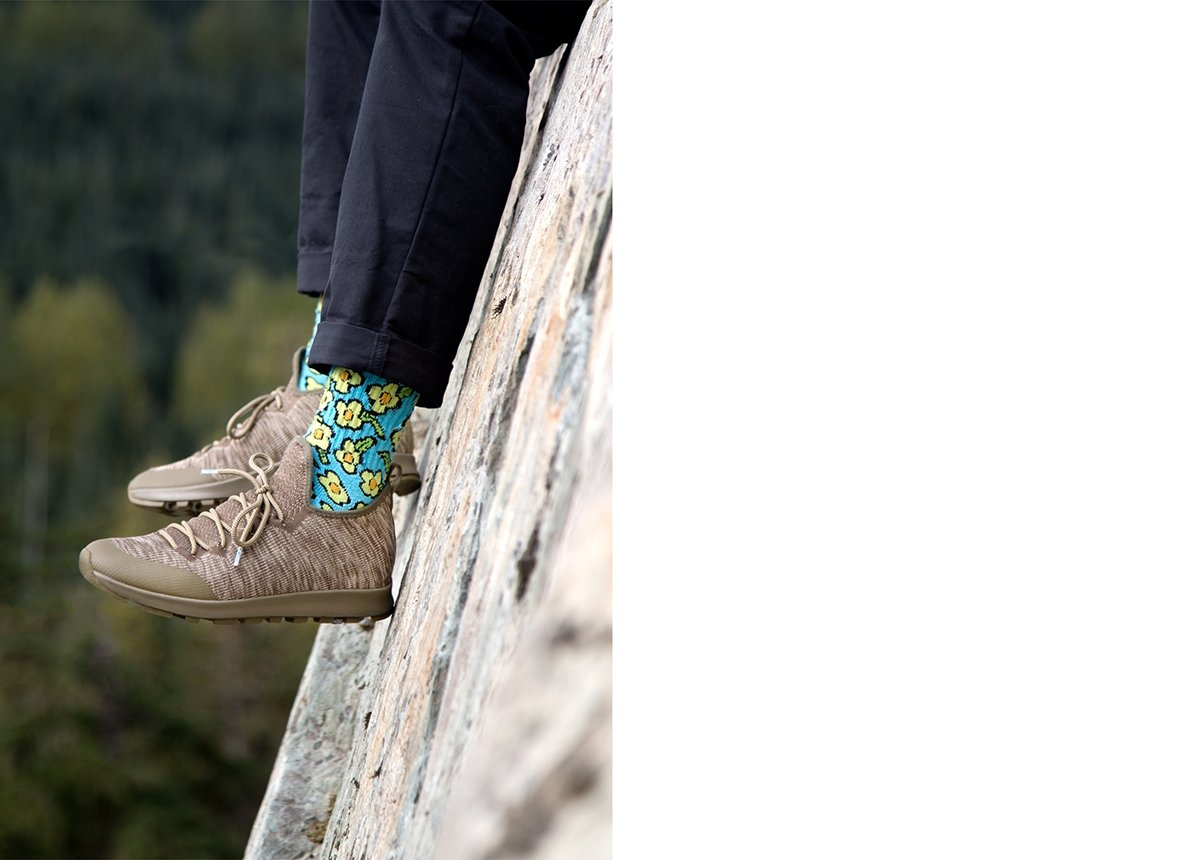 Feet wearing cool shoes and colorful socks on rocky cliff.
