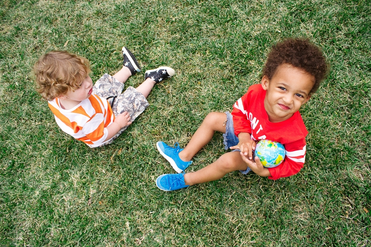 Two kids are sitting on a grass field wearing the Native Shoes Mercury Liteknit and the Jefferson in star print. One kid holds a globe.