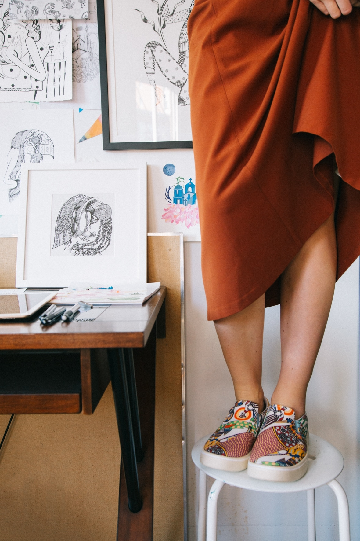 Ola Volo wearing the Native Shoes Ola Volo print collaboration shoes standing on a stool in her studio.
