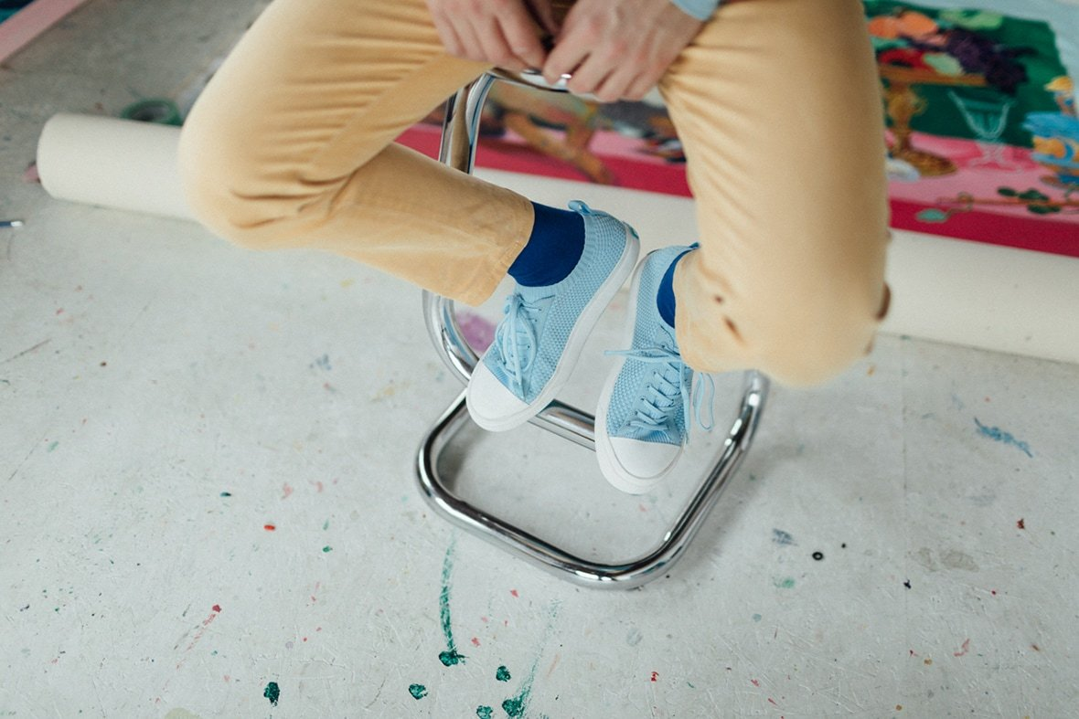 Andy Dixon posing on stool with colored pants and sky blue knit Jefferson shoes