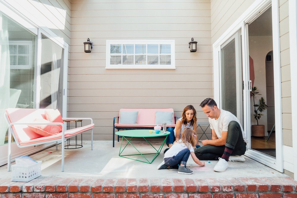 family outside on deck drawing on floor with chalk