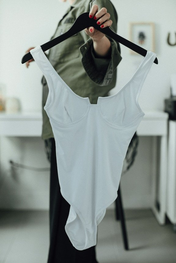 Beth Richards swimsuit designer holds one of her white one-piece swimsuits on hanger.