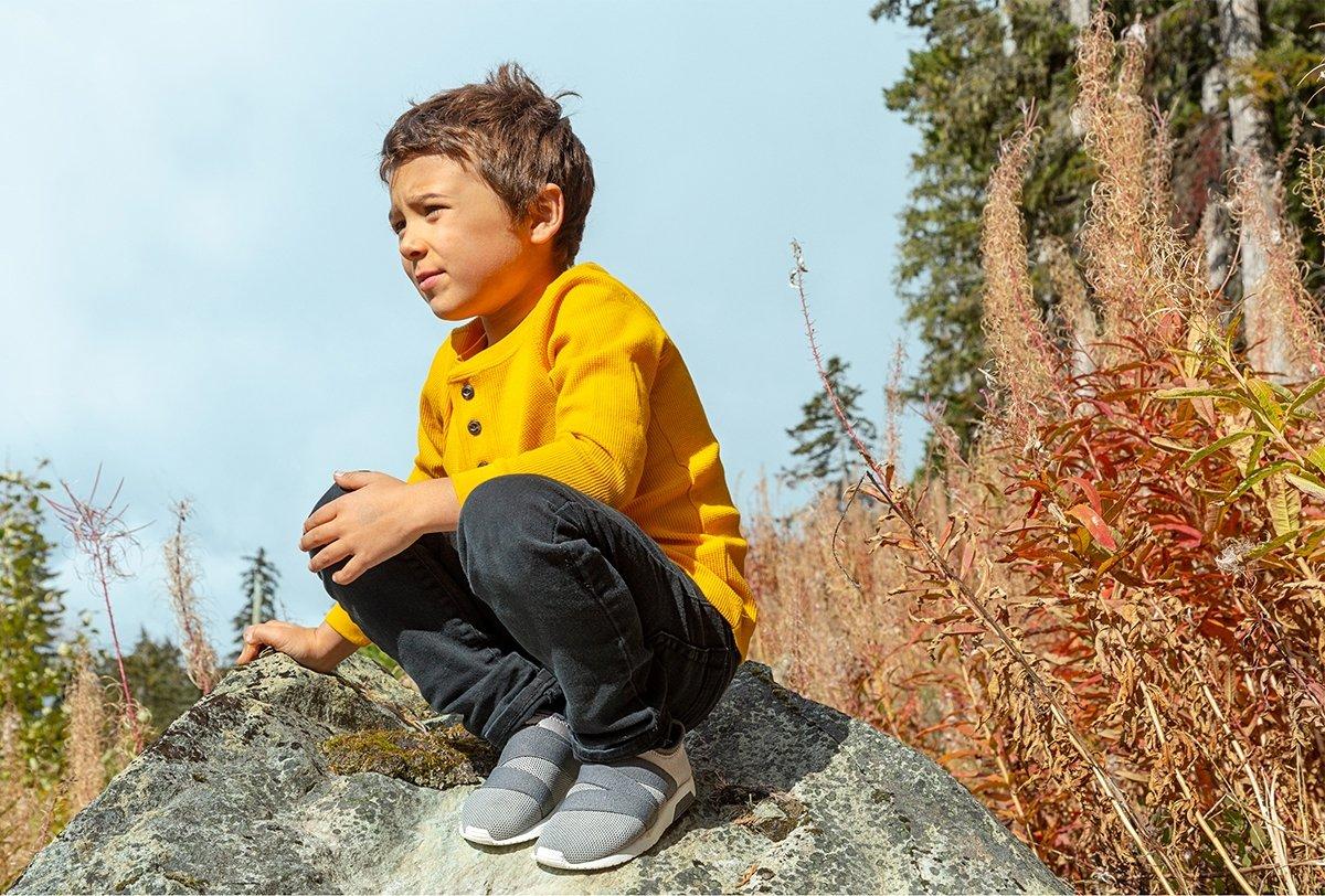Kid wearing slip-on sneakers in forest.