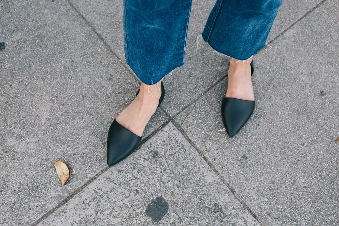 Women's feet wearing denim and black slip-on flat shoes with pointed toe