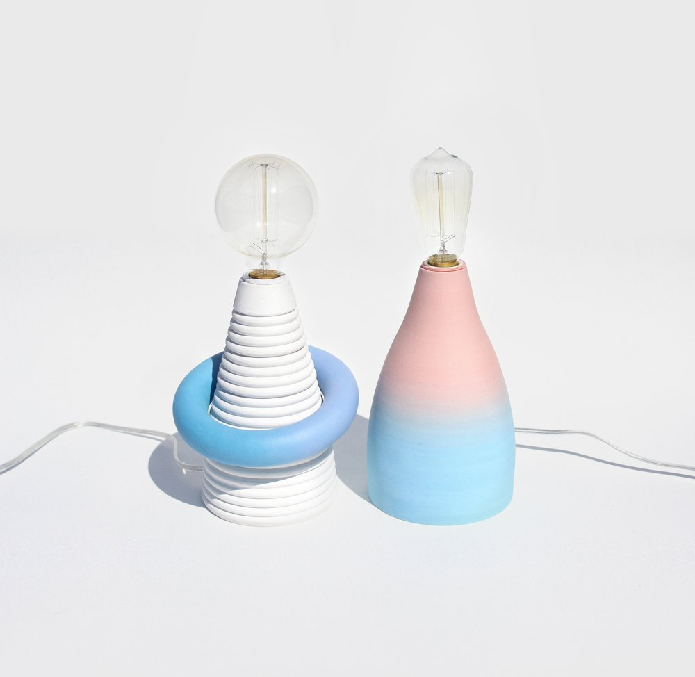 two lamps where one is white with circle bulb and another pink/blue with cylinder bulb