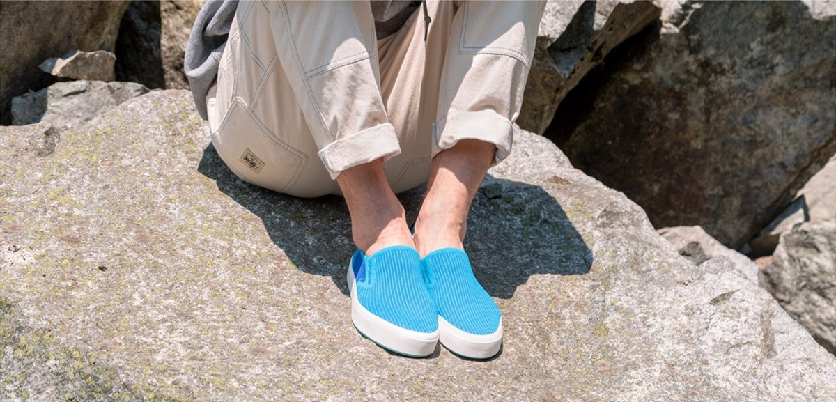 Person wearing blue slip-on stylish sneakers sitting on rock.