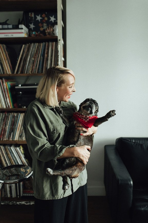 Beth Richards swimsuit designer in her living room smiling and holding her french bulldog in her arms.