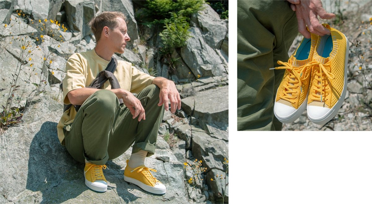 Guy wearing yellow trending sneakers crouches on rocky cliff. Guy holding yellow trending sneakers in hand.