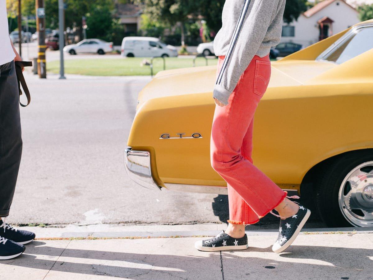 Girl in star-print sneakers wearing pink pants walks beside yellow vintage car