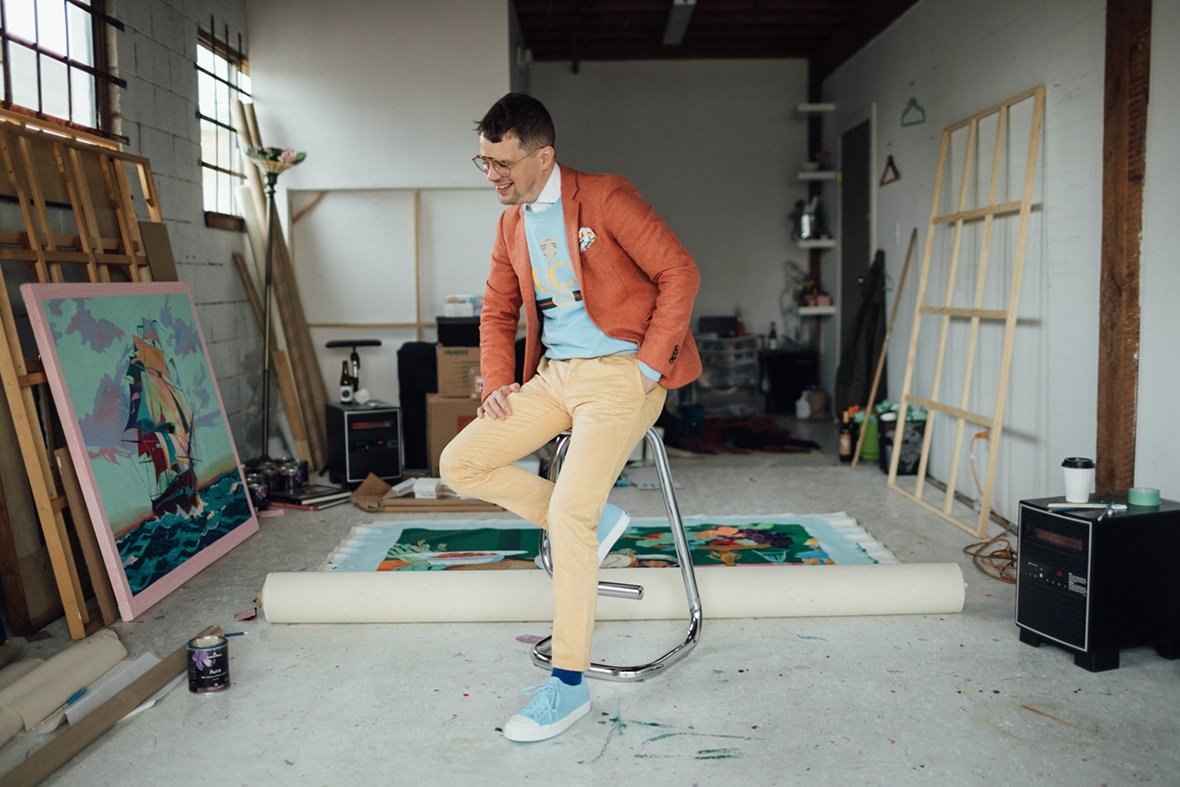 Andy Dixon laughing in his studio photographed on a stool wearing signature colors and blue Native Shoes.