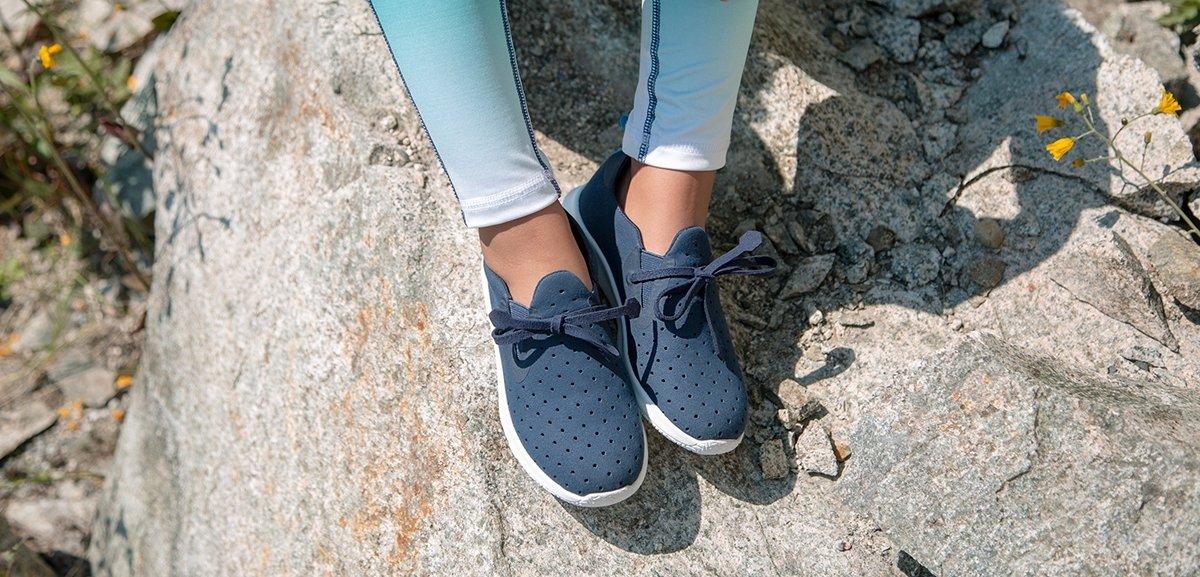 Girl is wearing slip on sneakers on rock.