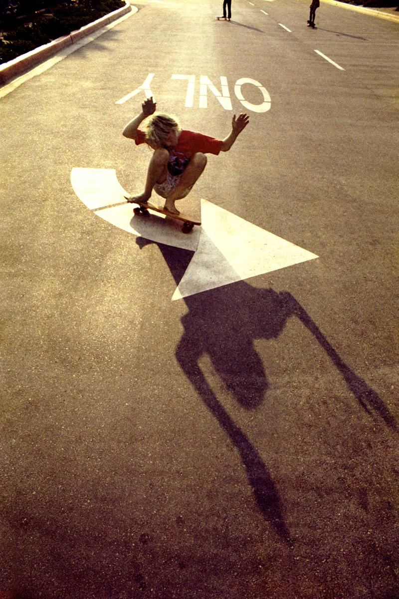 Hugh Holland photograph of kid skateboarding down road