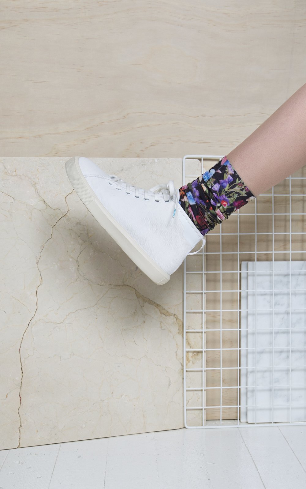 side view of white shoe on person with flower print socks