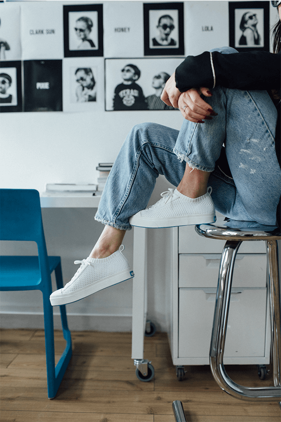 Waist down sitting on a stool wearing denim and The Jefferson 2.0 Liteknit low in white.